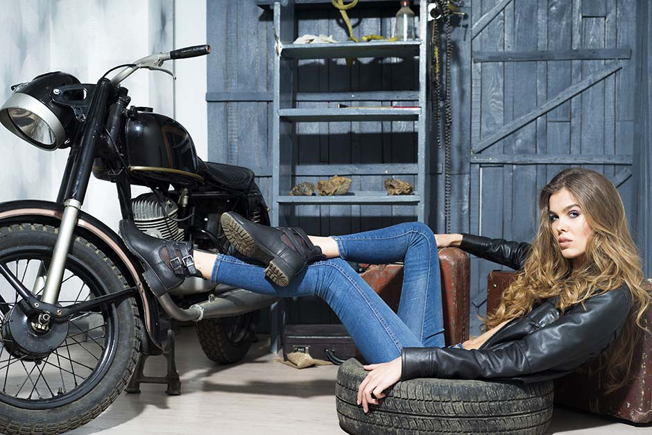 Tempting sexy young lady in black lace blouse and blue jeans lying near old fashioned motorcycle in garage interior on grey wooden wall background, horizontal picture