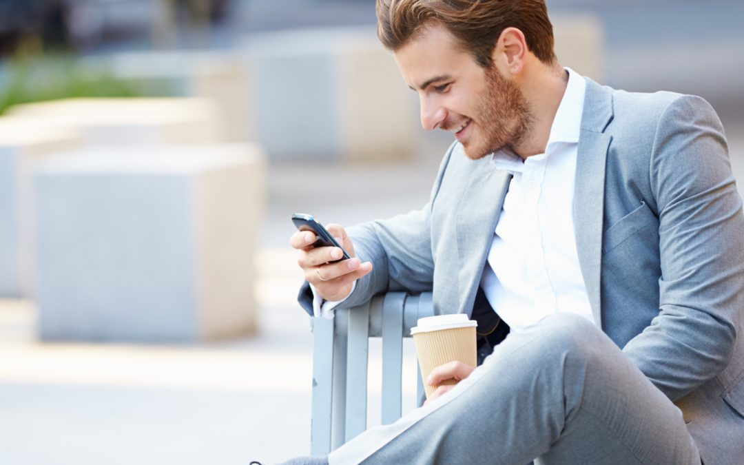 Young professional man sitting on bench looking at phone
